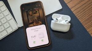 Das Foto zeigt ein iPhone 12 Pro mit geöffneter Netflix App. Daneben liegen die Airpods Pro im geöffneten Ladecase.
